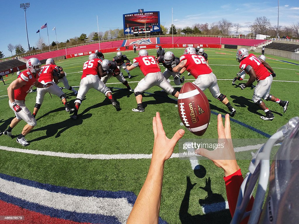 Quarterback Conor Bednarski of the Stony Brook Offense takes the snap from Center Mike White during their Spring Football Game at Kenneth P. LaValle Stadium on April 26, 2014 in Stony Brook, New York.