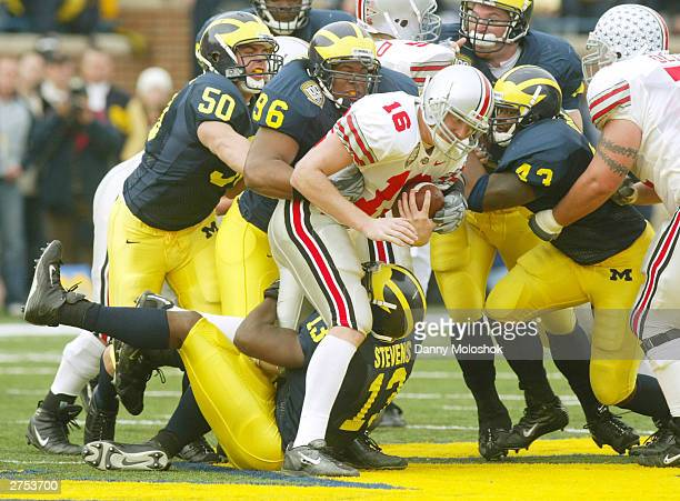 Quarterback Craig Krenzel of the Ohio State Buckeyes gets stopped as he attempts to run the ball through Jeremy Van Van Alstyne Larry Harrison Carl...