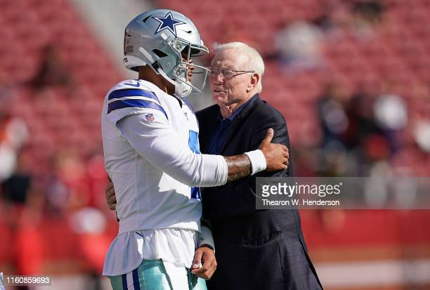 Quarterback Dak Prescott and team owner Jerry Jones of the Dallas Cowboys hug each other during pregame warm ups prior to the start of an NFL...