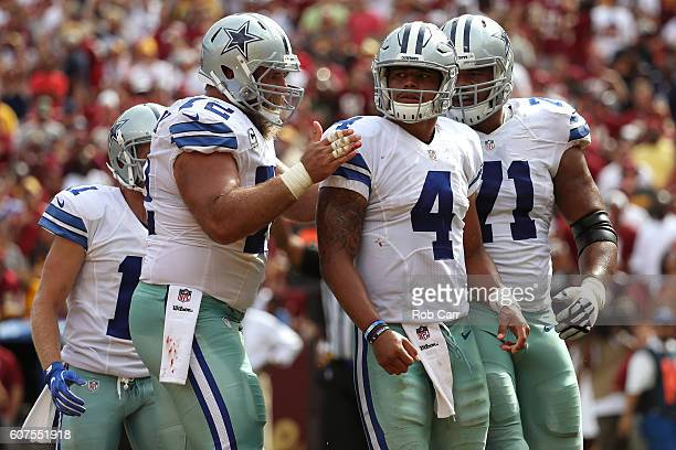 Quarterback Dak Prescott of the Dallas Cowboys celebrates with teammates center Travis Frederick and offensive guard La'el Collins after scoring a...