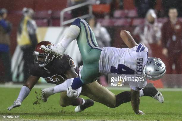 Quarterback Dak Prescott of the Dallas Cowboys is hit by inside linebacker Zach Brown of the Washington Redskins during the fourth quarter at FedEx...