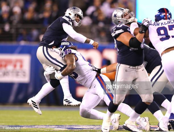 Quarterback Dak Prescott of the Dallas Cowboys is pressured to over throw the ball by defensive end Leonard Williams of the New York Giants in the...