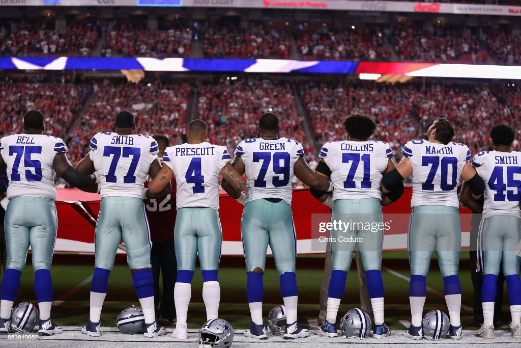 Quarterback Dak Prescott  4 of the Dallas Cowboys links arms with teammates  offensive tackle Tyron 4a6ae167cb1
