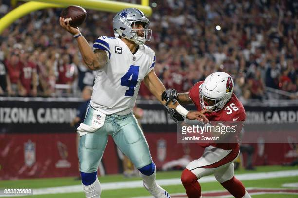 Quarterback Dak Prescott of the Dallas Cowboys throws a pass under pressure from safety Budda Baker of the Arizona Cardinals during the second half...