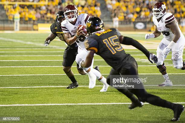Quarterback Dak Prescott of the Mississippi State Bulldogs scrambles and looks for an open player during their game against the Southern Miss Golden...