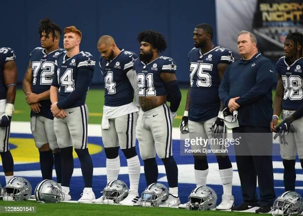 Quarterback Dak Prescott, running back Ezekiel Elliott and head coach Mike McCarthy of the Dallas Cowboys stand during a ceremony after warm ups...