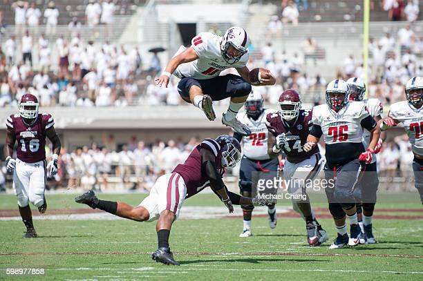Quarterback Dallas Davis of the South Alabama Jaguars leaps over defensive back Brandon Bryant of the Mississippi State Bulldogs for a first down at...