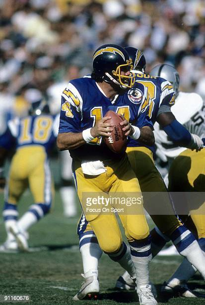 Quarterback Dan Fouts of the San Diego Chargers drops back to pass against the Los Angeles Raiders during an NFL football game October 21 1984 at...