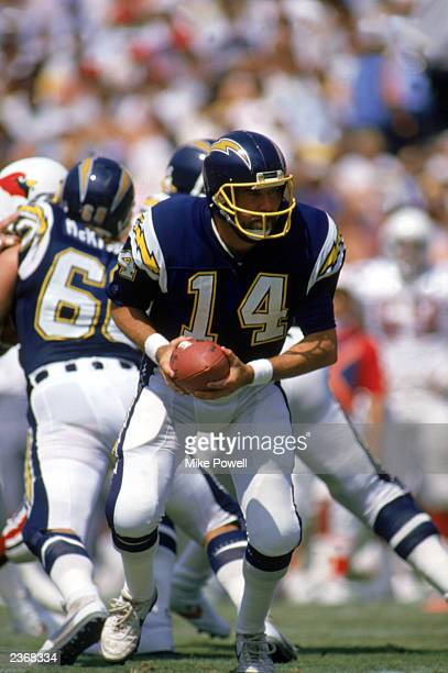 Quarterback Dan Fouts of the San Diego Chargers looks to hand off the ball during a game against the Arizona Cardinals at Jack Murphy Stadium during...