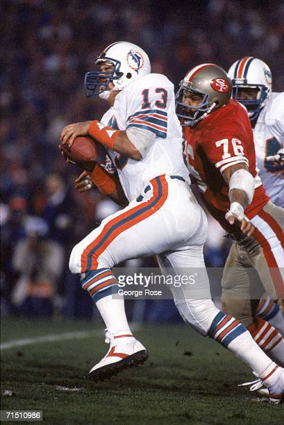 Quarterback Dan Marino of the Miami Dolphins gets sacked by defensive end Dwaine Board of the San Francisco 49ers during Super Bowl XIX at Stanford...
