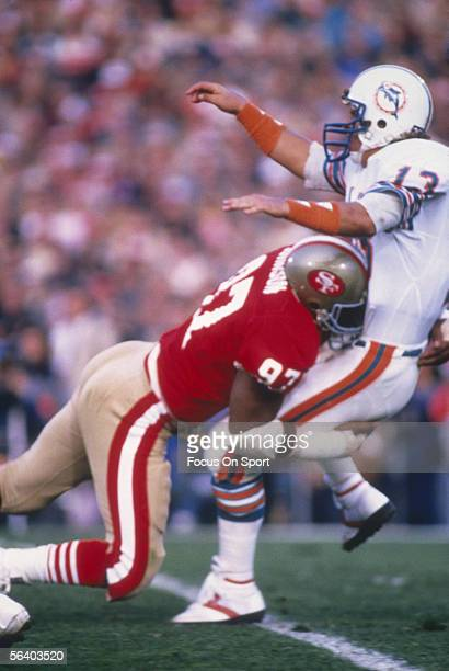 Quarterback Dan Marino of the Miami Dolphins is tackled while passing against the San Francisco 49ers during Super Bowl XIX at Stanford Stadium on...