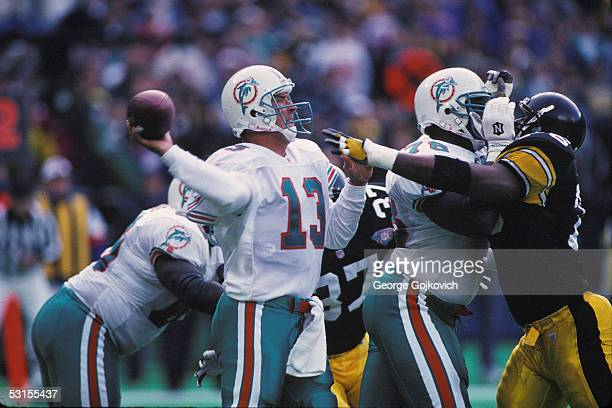 Quarterback Dan Marino of the Miami Dolphins passes as offensive lineman Richmond Webb blocks defensive lineman Kevin Henry of the Pittsburgh...