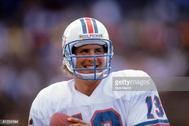 Quarterback Dan Marino of the Miami Dolphins smiles as he holds the ball during a game against the Atlanta Falcons in 1986 at Pro Player Stadium in...