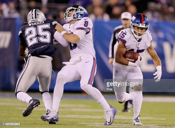 Quarterback Daniel Jones of the New York Giants blocks free safety Xavier Woods of the Dallas Cowboys for wide receiver Golden Tate as he carries the...