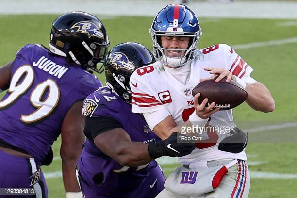 Quarterback Daniel Jones of the New York Giants is sacked by defensive tackle Justin Madubuike of the Baltimore Ravens at M&T Bank Stadium on...