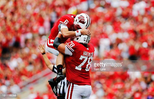 Quarterback Danny O'Brien of the Wisconsin Badgers leaps into the arms of teammate tackle Rob Havenstein after the Badgers score their first...
