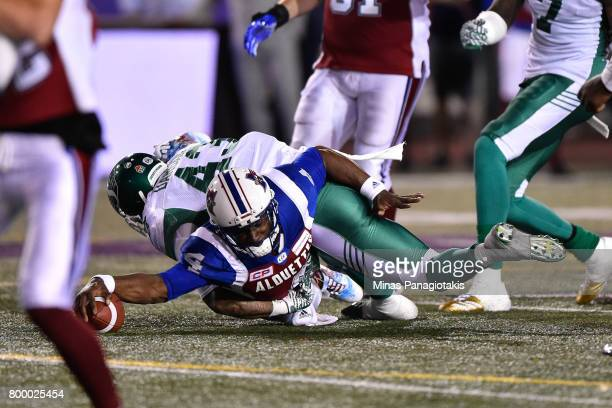 Quarterback Darian Durant of the Montreal Alouettes is taken down by defensive back Erick Dargan of the Saskatchewan Roughriders in the second half...