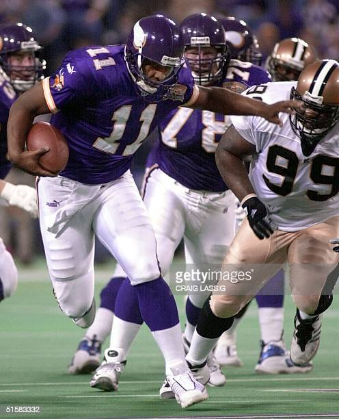 Quarterback Daunte Culpepper of the Minnesota Vikings stiff arms Norman Hand of the New Orleans Saints 06 January 2001 during the first half of their...