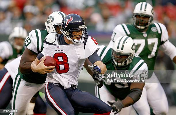 Quarterback David Carr of the Houston Texans is pressured by Bryan Thomas and Dewayne Robertson of the New York Jets at Giants Stadium on November 26...
