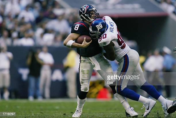 Quarterback David Carr of the Houston Texans is sacked by Kenny Holmes of the New York Giants during the NFL game at Reliant Stadium on November 24...