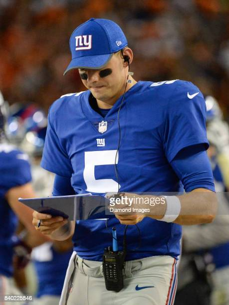 Quarterback Davis Webb of the New York Giants reads notes as he walks along the sideline in the first quarter of a preseason game on April 27 2017...