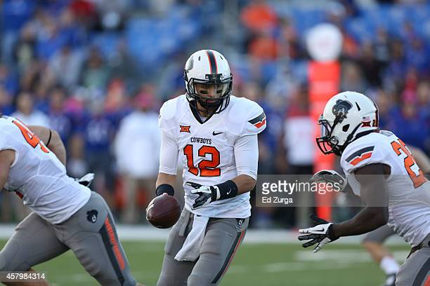 Quarterback Daxx Garman of the Oklahoma State Cowboys hands the ball running back Desmond Roland during a game against the Kansas Jayhawks at...
