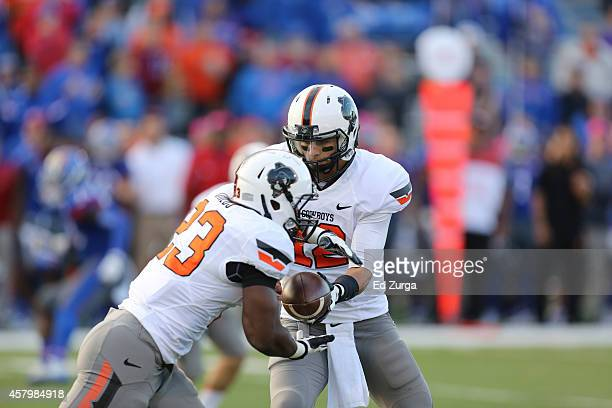Quarterback Daxx Garman of the Oklahoma State Cowboys hands the ball off to running back Rennie Childs in the fourth quarter at Memorial Stadium on...