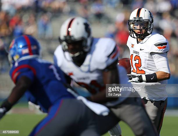 Quarterback Daxx Garman of the Oklahoma State Cowboys looks for running room against the Kansas Jayhawks in the second quarter at Memorial Stadium on...