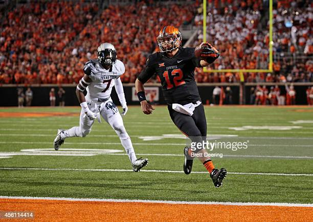 Quarterback Daxx Garman of the Oklahoma State Cowboys runs into the end zone in front of safety Josh Keys of the Texas Tech Red Raiders September 25,...