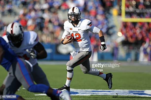 Quarterback Daxx Garman of the Oklahoma State Cowboys runs with the ball against the Kansas Jayhawks at Memorial Stadium on October 11 2014 in...