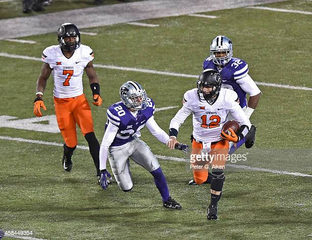 Quarterback Daxx Garman of the Oklahoma State Cowboys rushes against free safety Dylan Schellenberg of the Kansas State Wildcats during the first...