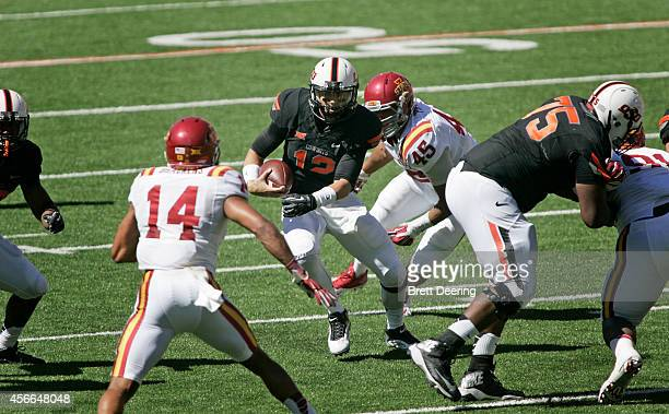 Quarterback Daxx Garman of the Oklahoma State Cowboys scrambles under pressure from defensive end Dale Pierson of the Iowa State Cyclones October 4...