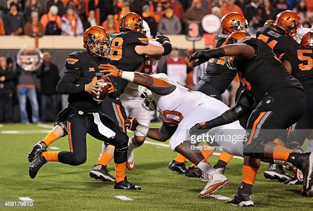 Quarterback Daxx Garman of the Oklahoma State Cowboys tries to avoid defensive tackle Malcom Brown of the Texas Longhorns November 15 2014 at Boone...