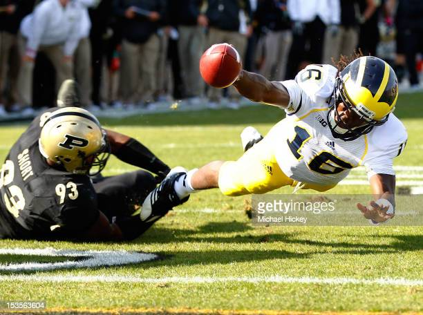 Quarterback Denard Robinson of the Michigan Wolverines dives for a touchdown but was eventually ruled down and short of the goal line as defensive...