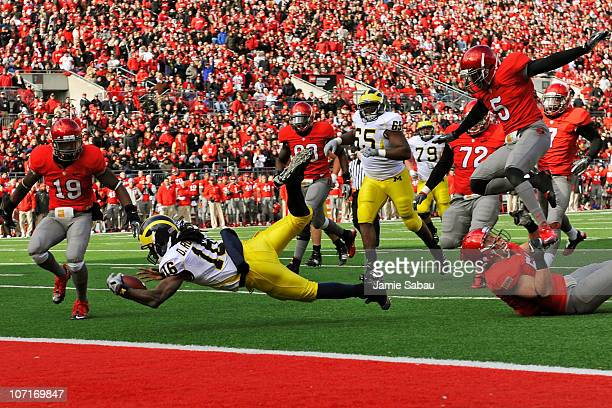Quarterback Denard Robinson of the Michigan Wolverines is tripped up just shy of the goal line by Ross Homan of the Ohio State Buckeyes at Ohio...