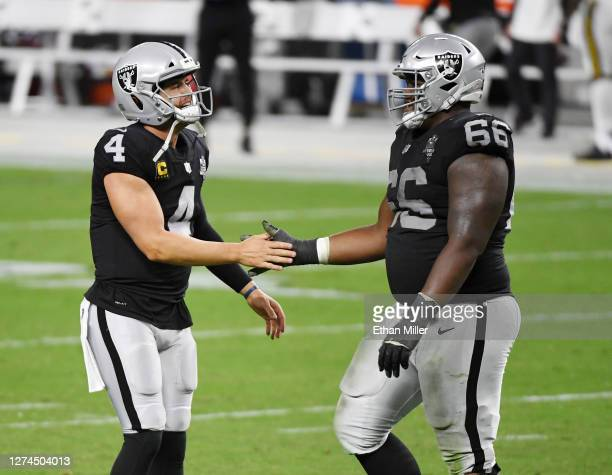 Quarterback Derek Carr and offensive guard Gabe Jackson of the Las Vegas Raiders celebrate on the field during the second half of the NFL game...