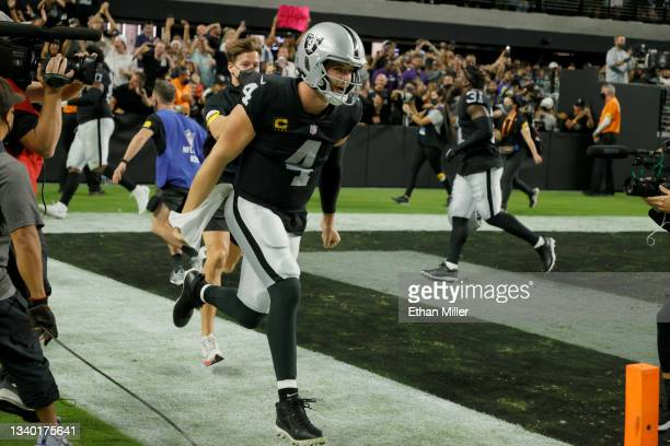 Quarterback Derek Carr of the Las Vegas Raiders celebrates after throwing a 31-yard touchdown pass to wide receiver Zay Jones in overtime to defeat...