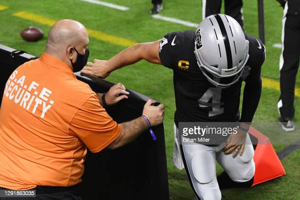 Quarterback Derek Carr of the Las Vegas Raiders holds his leg after coming off the field during the first half against the Los Angeles Chargers at...
