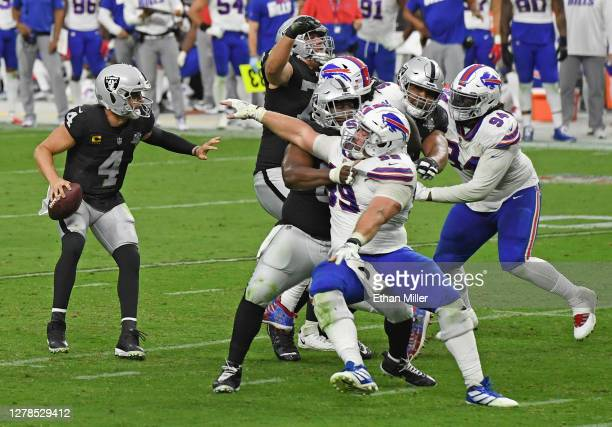 Quarterback Derek Carr of the Las Vegas Raiders looks to pass as center Rodney Hudson of the Raiders blocks defensive tackle Harrison Phillips of the...