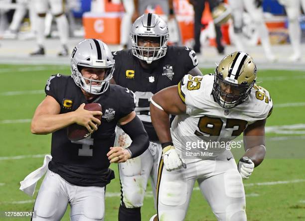 Quarterback Derek Carr of the Las Vegas Raiders rushes under pressure from defensive tackle David Onyemata of the New Orleans Saints ahead of Rodney...