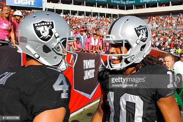 Quarterback Derek Carr of the Oakland Raiders and wide receiver Seth Roberts celebrate in the back of the end zone after connecting on the winning...