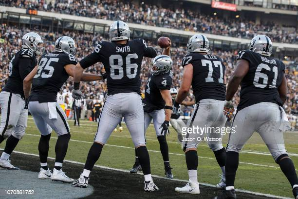 Quarterback Derek Carr of the Oakland Raiders celebrates with tight end Lee Smith after after a touchdown against the Pittsburgh Steelers during the...