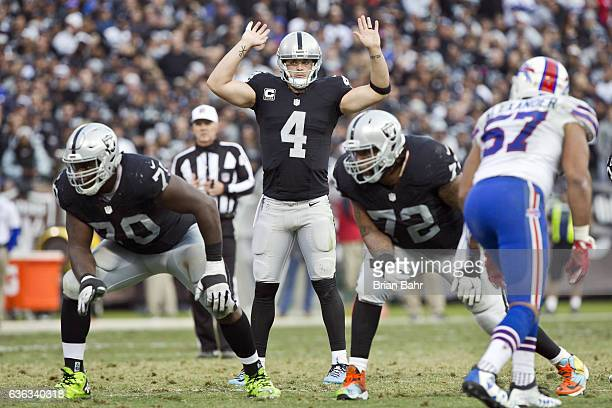 Quarterback Derek Carr of the Oakland Raiders holds his hands up before a play against the Buffalo Bills in the fourth quarter on December 4 2016 at...
