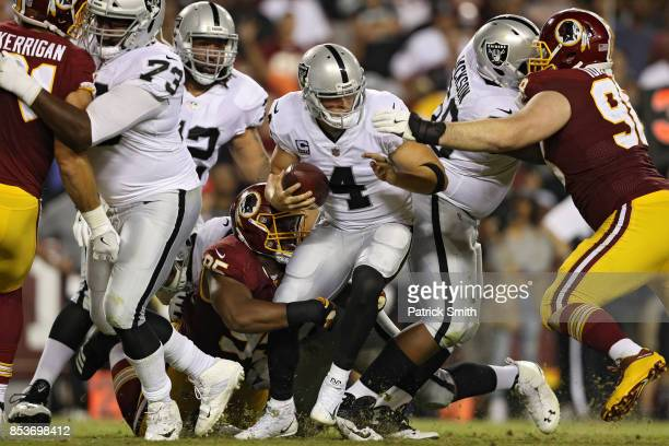 Quarterback Derek Carr of the Oakland Raiders is sacked by defensive end Jonathan Allen of the Washington Redskins during the second half at...