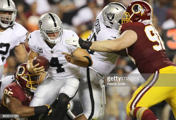 Quarterback Derek Carr of the Oakland Raiders is taken down by tight end Vernon Davis of the Washington Redskins in the third quarter at FedExField...