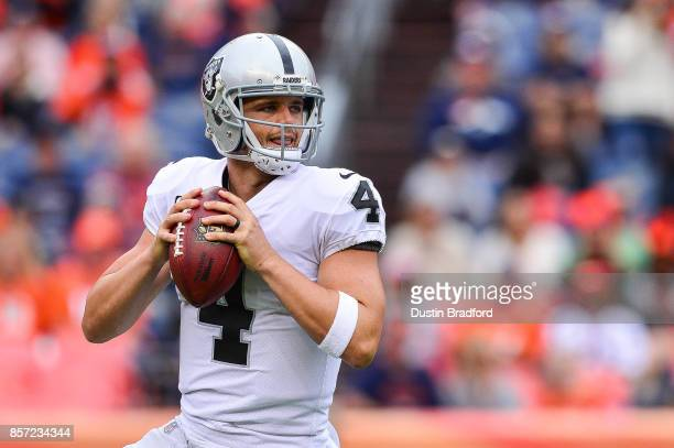 Quarterback Derek Carr of the Oakland Raiders looks to pass against the Denver Broncos during a game at Sports Authority Field at Mile High on...