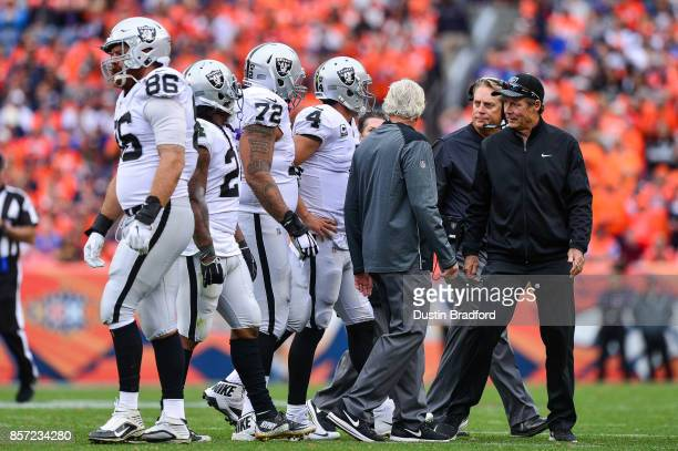 Quarterback Derek Carr of the Oakland Raiders walks off the field with head coach Jack Del Rio after sustaining an injury in the third quarter of a...