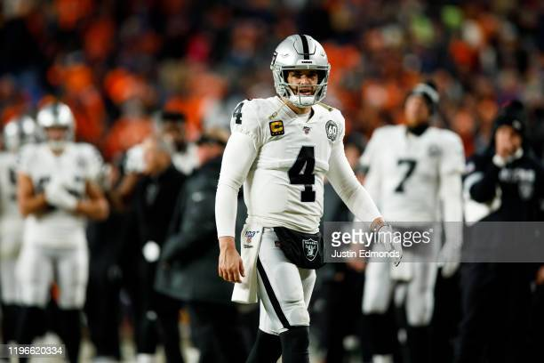 Quarterback Derek Carr of the Oakland Raiders walks on the field against the Denver Broncos during the fourth quarter at Empower Field at Mile High...