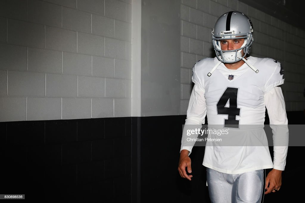Quarterback Derek Carr #4 of the Oakland Raiders walks out onto the field before the NFL game against the Arizona Cardinals at the University of Phoenix Stadium on August 12, 2017 in Glendale, Arizona.