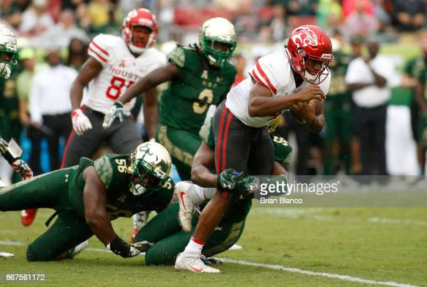 Quarterback D'Eriq King of the Houston Cougars is sacked by defensive end Josh Black of the South Florida Bulls during the first quarter of an NCAA...